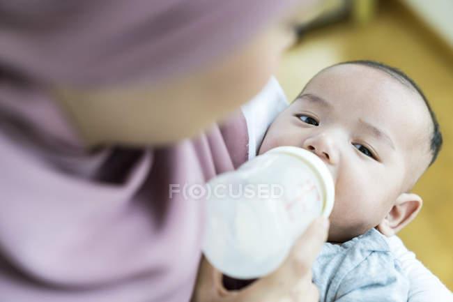 Madre che alimenta il suo bambino a casa — Foto stock