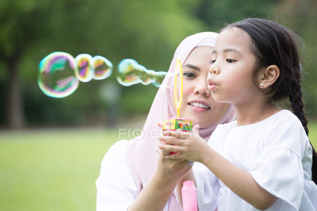 Cute asian mother and daughter spending time together at park — Stock Photo