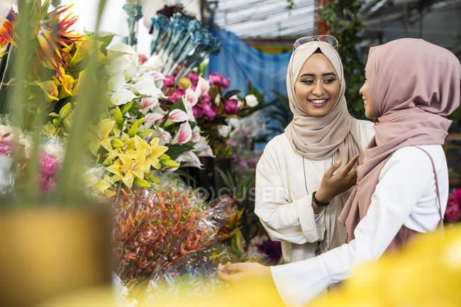 Damas musulmanas jóvenes comprando flores . - foto de stock