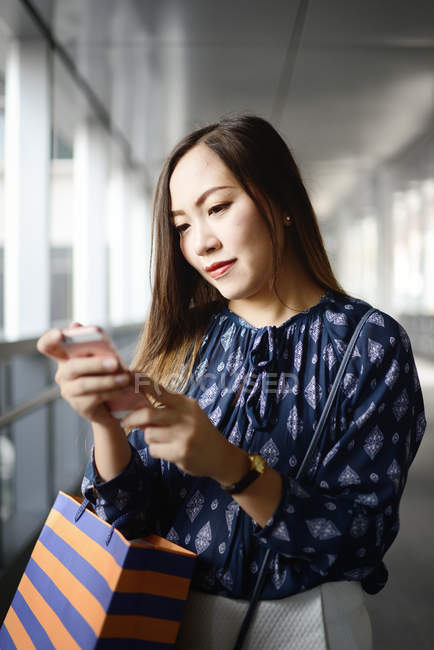 Happy  beautiful asian woman at shopping using smartphone — Stock Photo