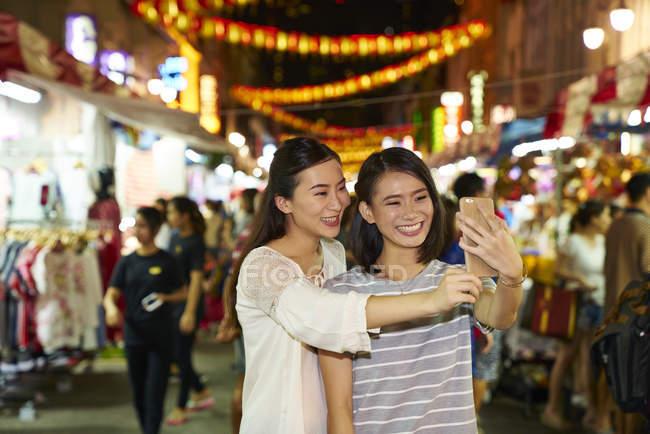 Jeunes amis asiatiques heureux passer du temps ensemble au Nouvel An chinois et de prendre selfie — Photo de stock