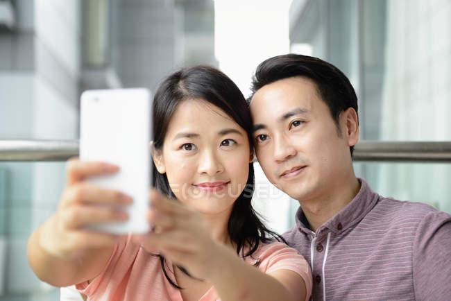 Adulto asiatico coppia insieme prendendo selfie a casa — Foto stock