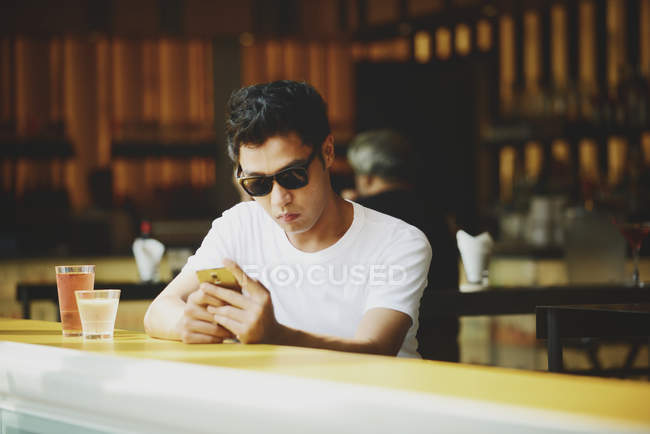 Young attractive asian man using smartphone in cafe — Stock Photo