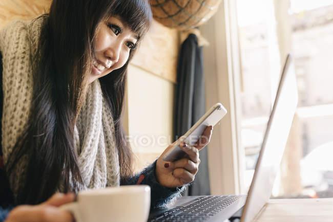 Jovem atraente asiático mulher usando smartphone no café — Fotografia de Stock