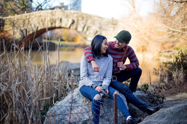 Молодая пара, сидящая и отдыхающая в центральном парке, Нью-Йорк, США — стоковое фото