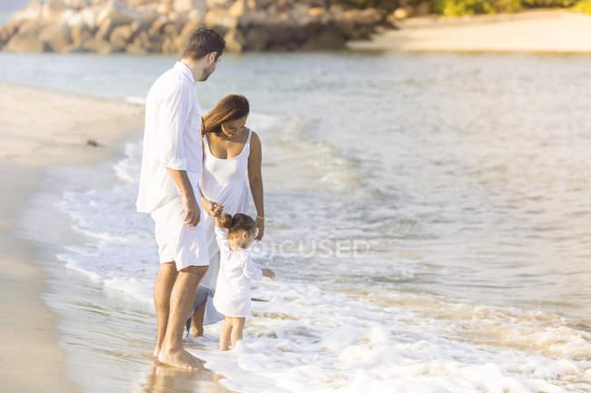 Счастливая молодая семья, проводящая время вместе на пляже — стоковое фото