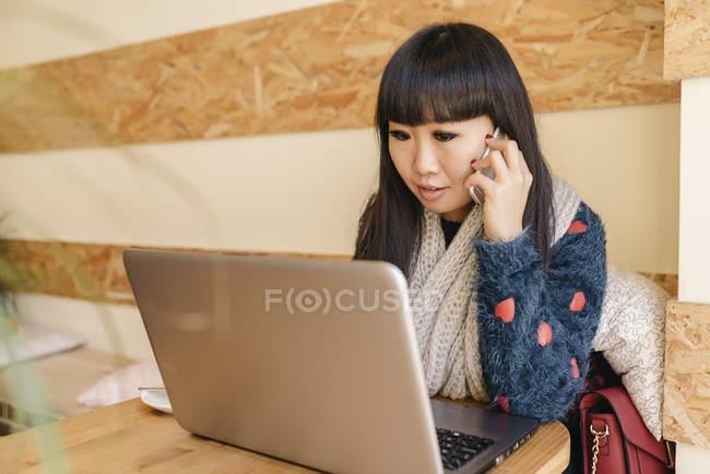 Jeune femme asiatique attrayante à l'aide de smartphone dans café — Photo de stock