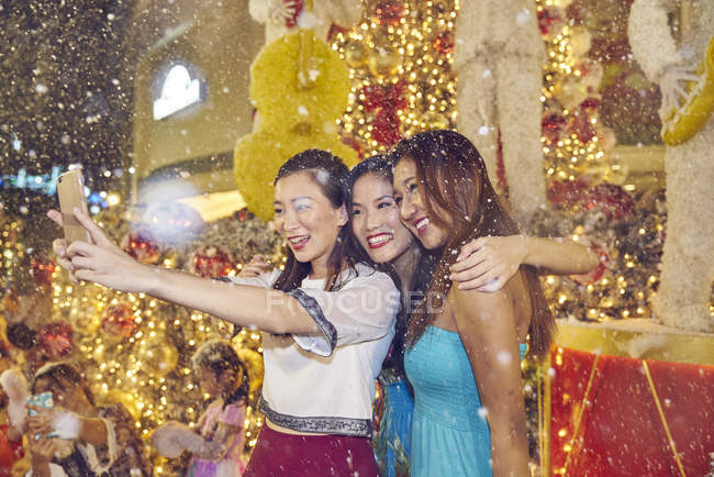 Young attractive asian women at christmas shopping taking selfie — Stock Photo
