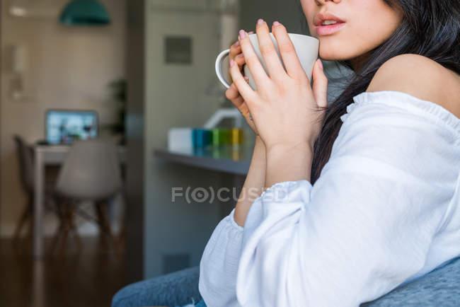 Jeune Chinoise sur un canapé buvant du café — Photo de stock