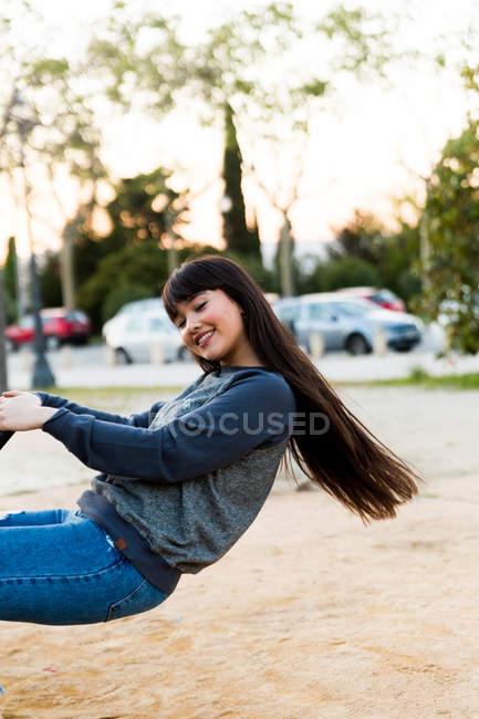 Junge eurasische Frau reitet Schaukel im Park in Barcelona — Stockfoto