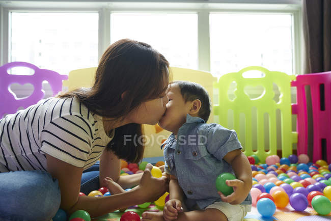 Mutter beim Binden mit Baby im Spielzimmer — Stockfoto
