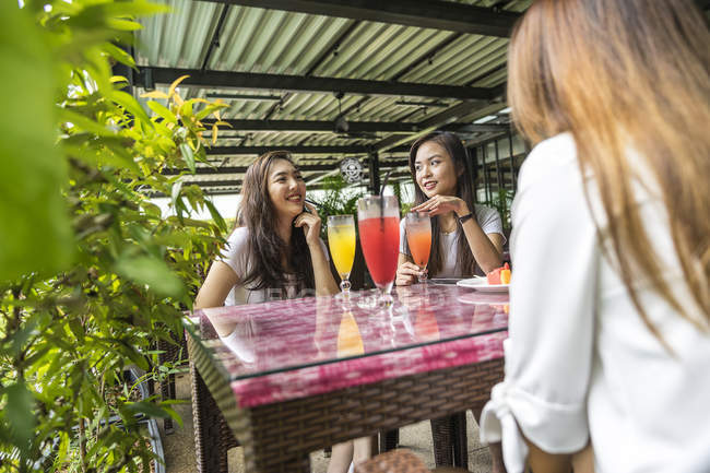 Three girls chilling over fruit juice. — Stock Photo
