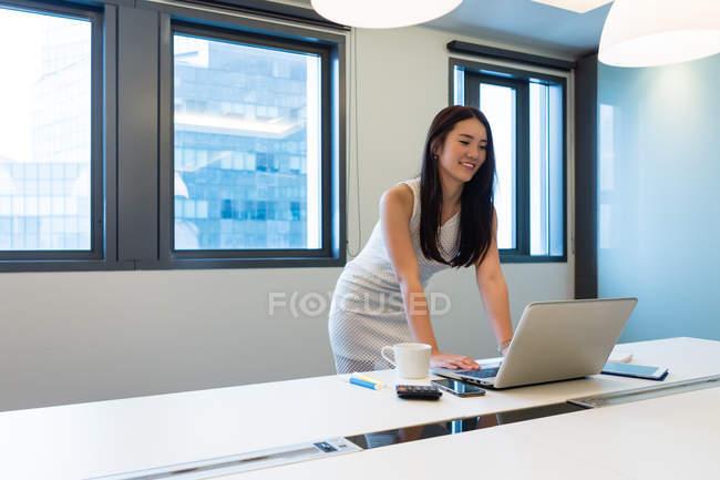 Jovem bela mulher asiática trabalhando com laptop no escritório moderno — Fotografia de Stock