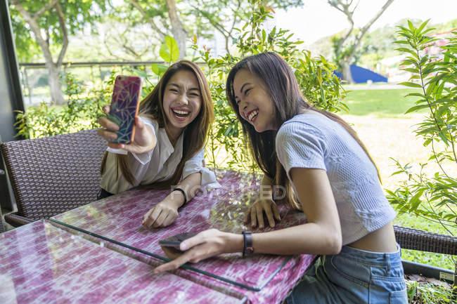 Dos jóvenes hermosas damas tomando una selfie . - foto de stock