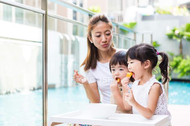 Kinder genießen snack zusammen mit ihrer Mutter. — Stockfoto