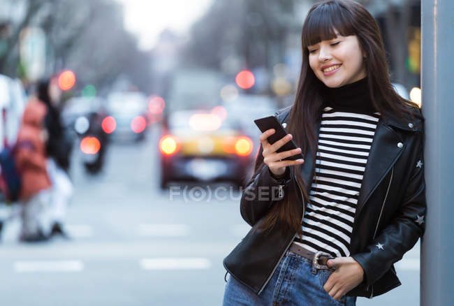 Молодая привлекательная азиатка в городе с помощью смартфона — стоковое фото