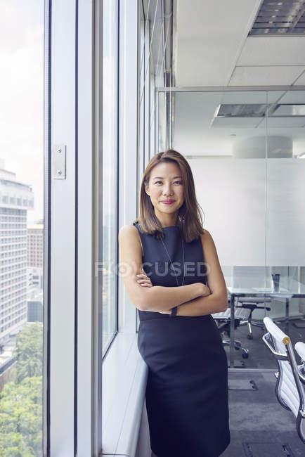 Jovem asiático mulher de negócios na janela no escritório moderno — Fotografia de Stock