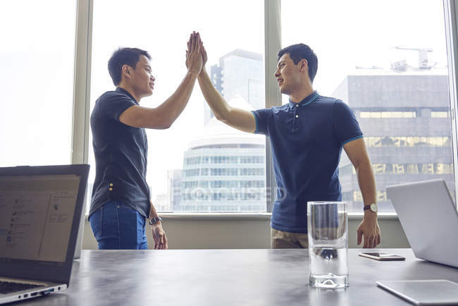 Giovani uomini d'affari asiatici dando cinque a ufficio moderno — Foto stock
