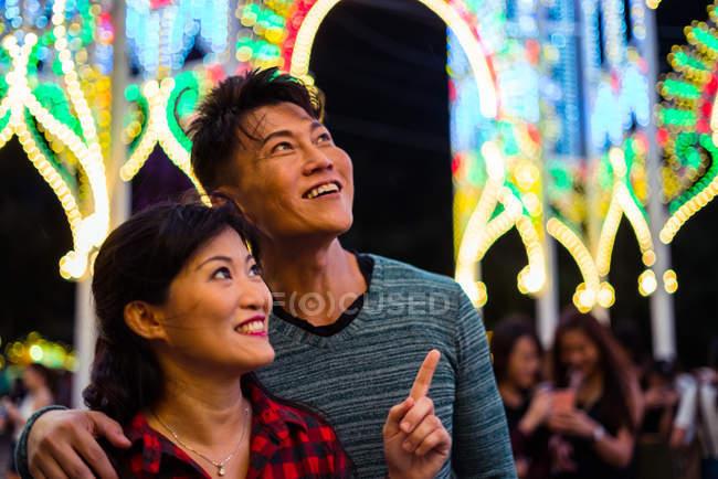 Felice coppia asiatica trascorrere del tempo insieme nel parco divertimenti a Natale — Foto stock
