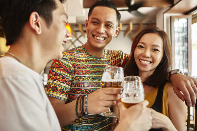Happy young asian friends together in bar having beer — Stock Photo