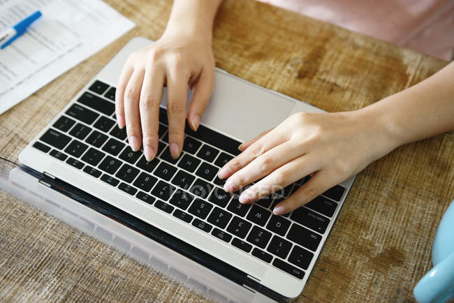 Cropped image of woman using laptop at home — Stock Photo