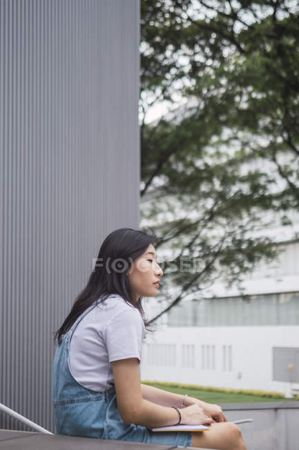 Young asian college student studying near campus — Stock Photo
