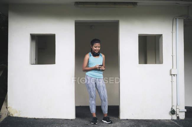 Jeune femme sportive asiatique à l'aide de smartphone — Photo de stock