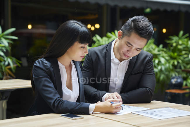 Young asian business couple working together in cafe — Stock Photo