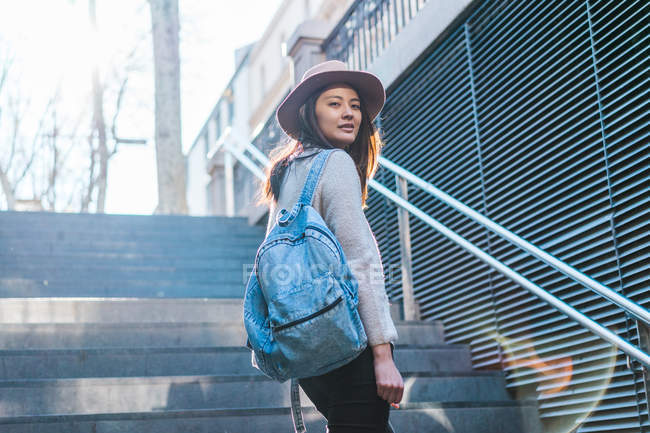 Young attractive asian woman with backpack on stairs — Stock Photo