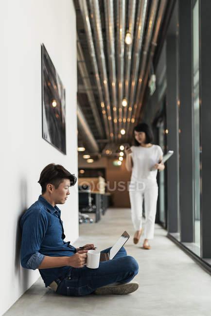 Due giovani asiatici sul lavoro con il computer portatile in ufficio moderno — Foto stock