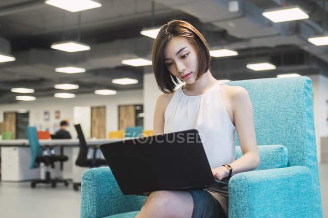 Donna d'affari di successo utilizzando il computer portatile in ufficio moderno — Foto stock