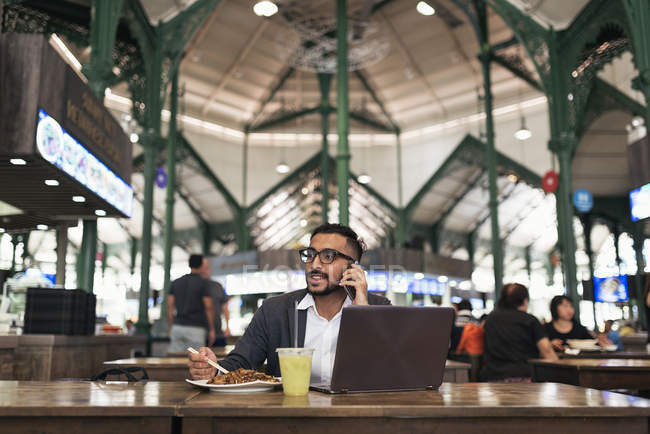 Handsome indian business man using smartphone and eating in cafe — Stock Photo