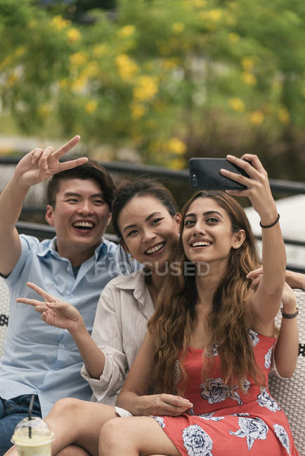 Group of young asian friends taking selfie outdoors — Stock Photo