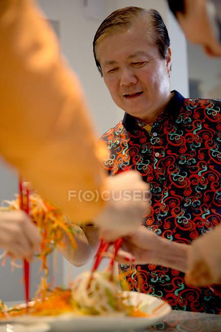 Старик с семьей ужинают вместе за китайским новогодним столом — стоковое фото