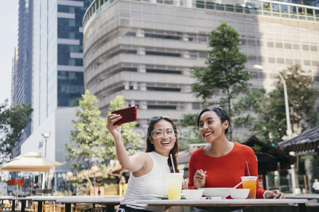 Young asian female friends together taking selfie in cafe — Stock Photo
