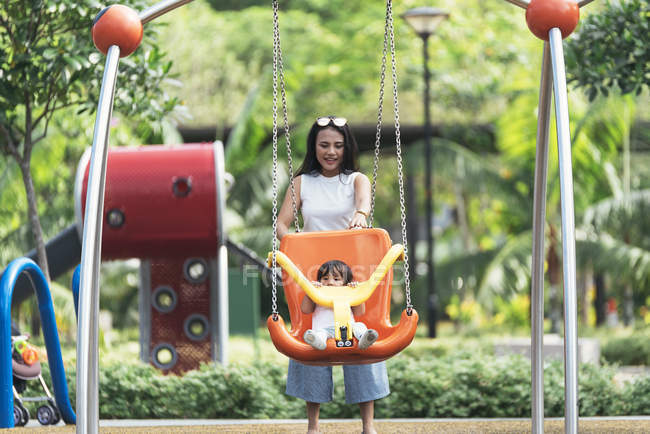 Cute adorable asian little girl on playground with mother — Stock Photo