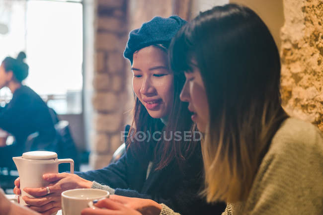 Young casual asian girls drinking coffee in cafe — Stock Photo