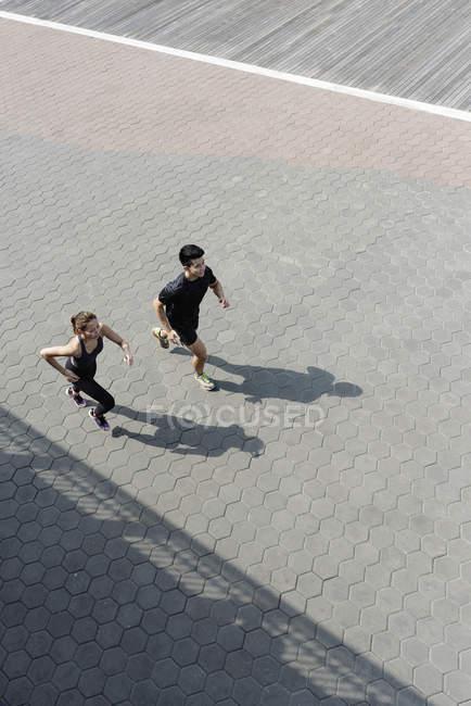 Повышенный вид азиатской пары, бегущей вместе — стоковое фото