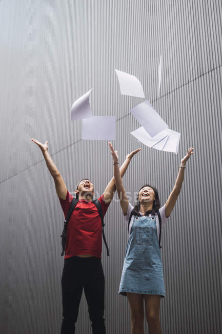 Young asian college students throwing paper in the air — Stock Photo