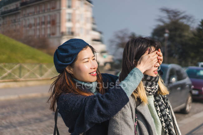 Young casual asian girls, one closing eyes to another — Stock Photo