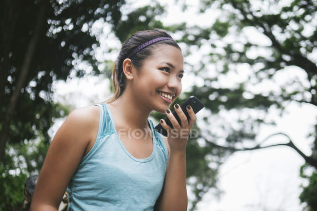 Joven asiático deportivo mujer usando smartphone en parque - foto de stock