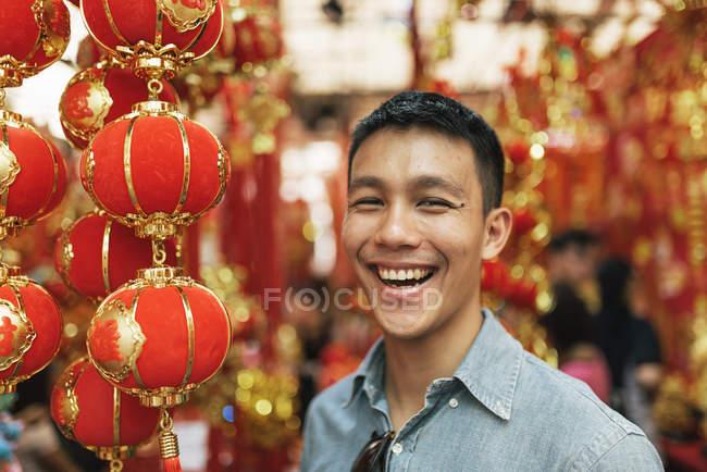 Giovane felice uomo asiatico sorridente in Chinatown — Foto stock