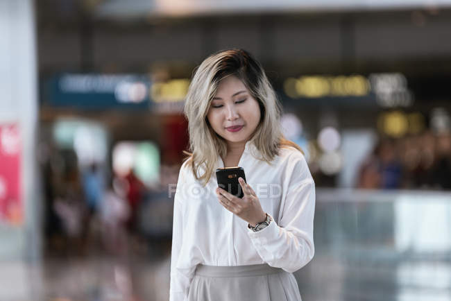 Successful asian business woman using smartphone in airport — Stock Photo