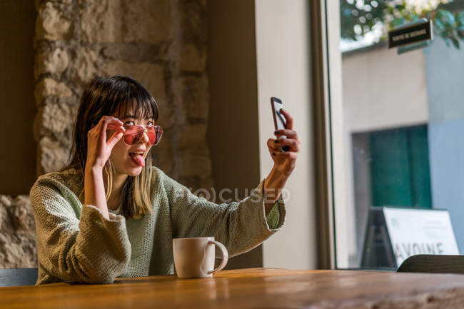 Young casual asian girl taking selfie in cafe — Stock Photo