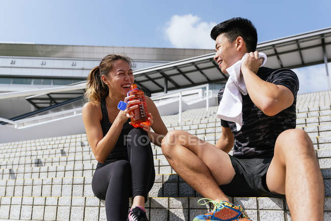 Young sporty couple relaxing and drinking water on stairs — Fotografia de Stock