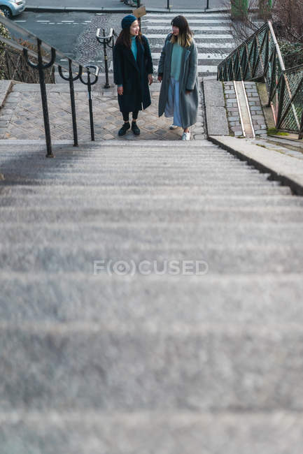Young casual asian girls standing near steps — Stock Photo