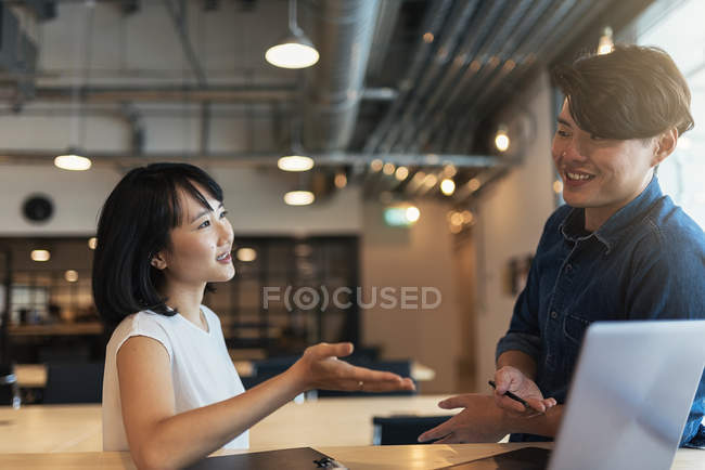 Two young asian people at work with laptop in modern office — Stock Photo