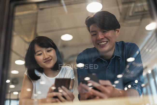 Zwei junge Asiaten mit Smartphones im modernen Büro — Stockfoto