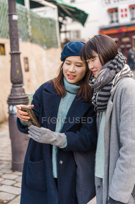 Young casual asian girls using smartphone in city — Stock Photo