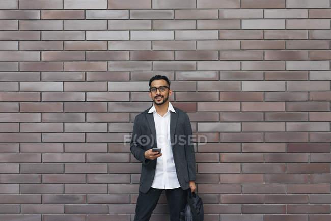 Красивий Індійська бізнесменом за допомогою смартфона проти цегляна стіна — стокове фото